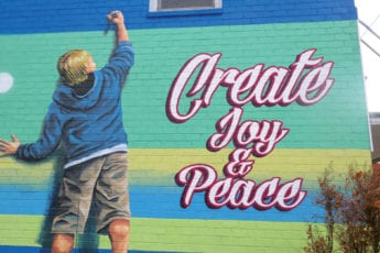 """painting on brick of a boy drawing saying """"Create Joy and Peace"""""""