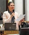 Barbara Fleischauer holding a mic reading off a paper