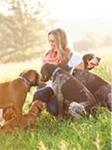Chelsea Stanley surrounded by dogs varying in breeds and sizes