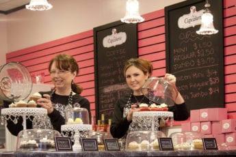 Cupcakerie employees setting up cupcake displays