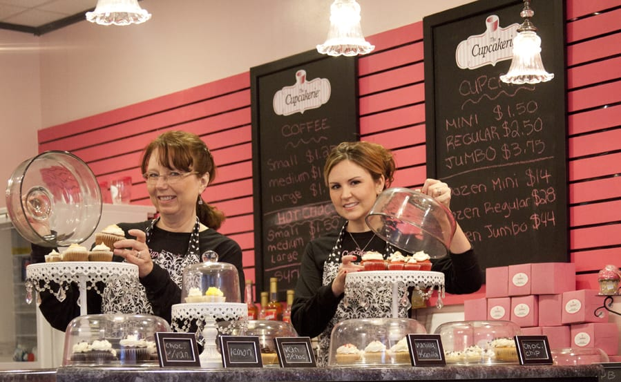Cupcakerie employees setting up cupcake displays