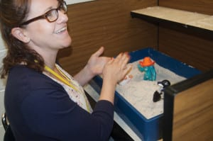 A woman playing with sand from a box sitting on a desk