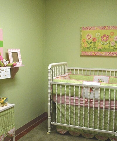 Nursery/ baby bedroom with green walls, furniture, and toys