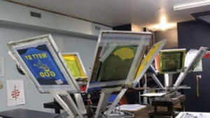 Screens for screen printing hanging to dry with designs on them.
