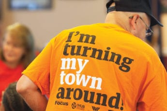 "Man in a bright orange t-shirt that reads ""I'm turning my town around"" on the back"