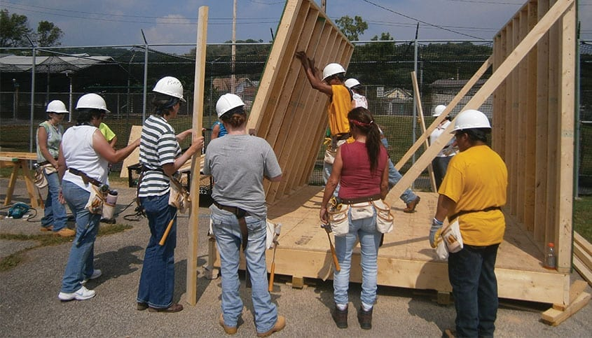 Women lifting up a wall to help build a house