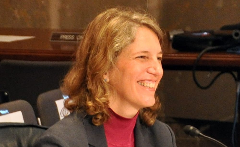 Sylvia Mathews Burwell smiling to someone talking to her off camera